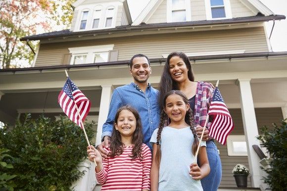 A family on the front porch of their home waving American flags.