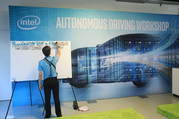 A person writing on a whiteboard at Intel's Autonomous Driving Workshop.