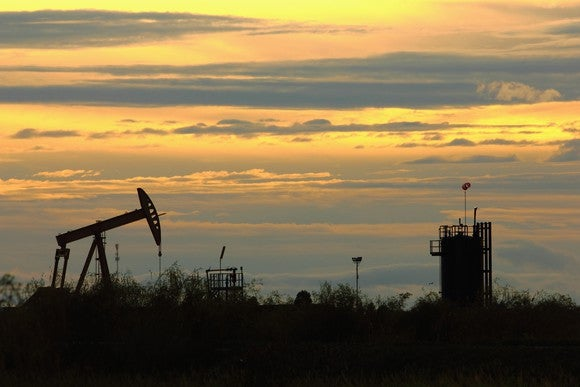 An oil pump in a grassy field at sunset.