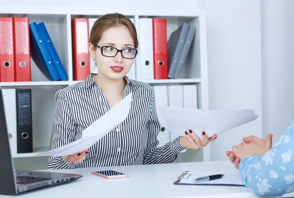 Female professional holding papers with rude expression on her face