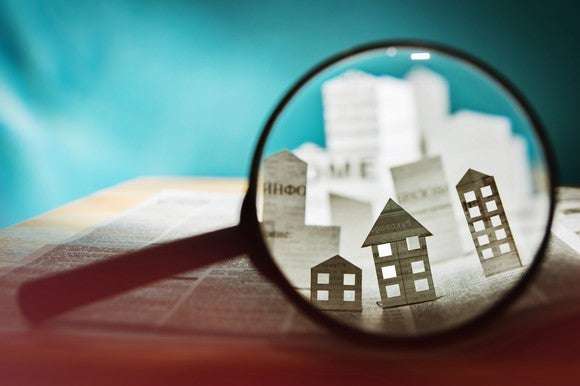 Magnifying glass highlighting 3D paper shapes of houses and buildings popping up from a newspaper