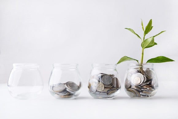 A row of four glass jars with successively more coins in each and the final one having a plant growing out of it.