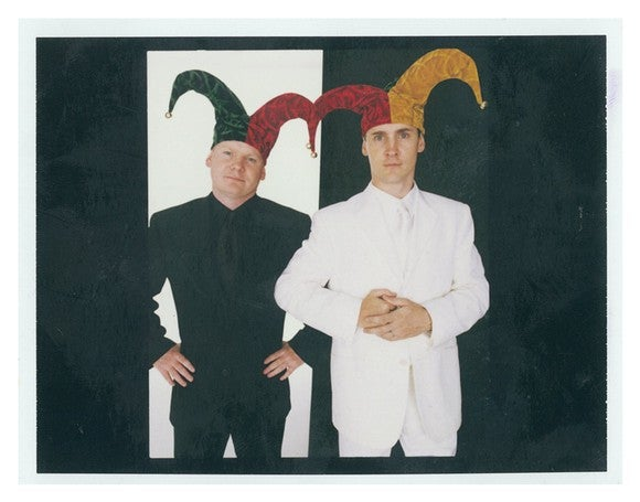 Two men (Tom and David Gardner), one in an all-black suit and the other in an all-white suit, both wearing jester caps, in front of black and white backgrounds.