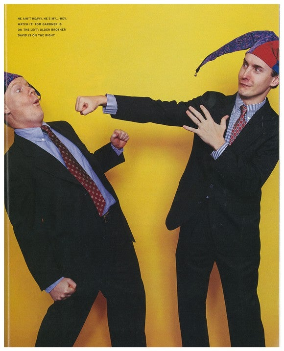 Two men in jester hats and suits, one fake-punching the other.