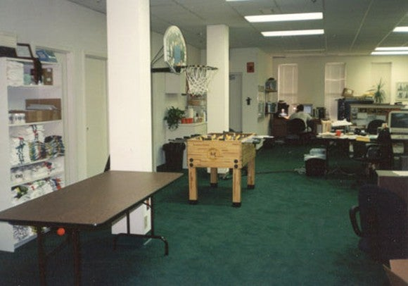 Room in an office building -- bookshelf with towels and books stacked on it, a basketball hoop, an empty brown table, and a foosball table. Desks in the corner.