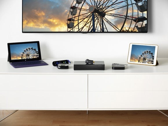 Various computing devices on a table with a television mounted on the wall.