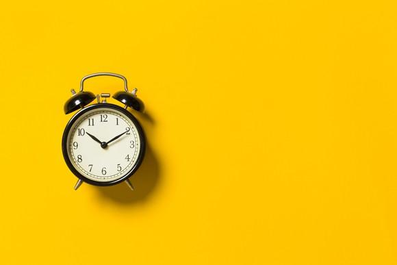 A black analog alarm clock on a yellow background.