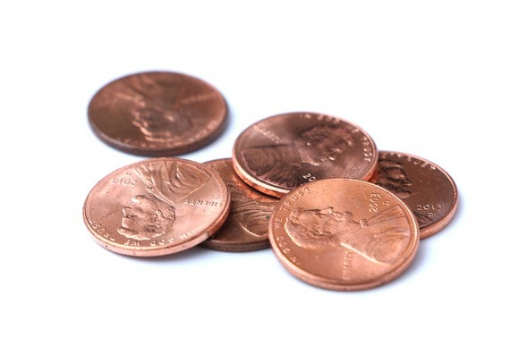 Six pennies forming a loose pile on a plain white background.