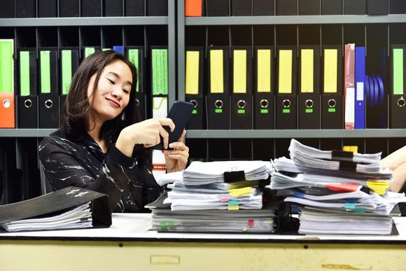 Young female checks her phone at her desk while stacks of papers and binders pile up