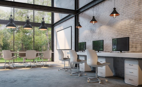 Modern office with exposed brick and glass walls overlooking garden.
