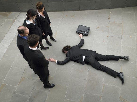Business people looking down at a peer laying flat on his stomach on the ground.