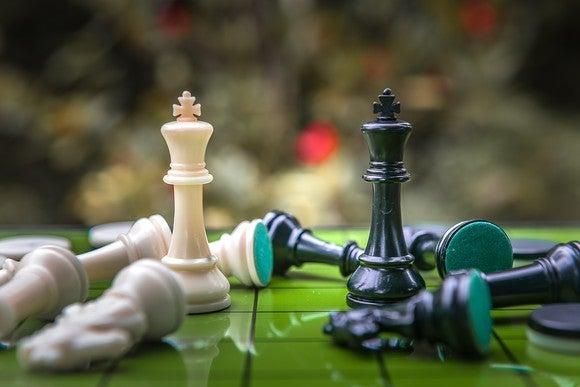 A white chess piece king facing off against a black chess piece king amid a pile of fallen pieces