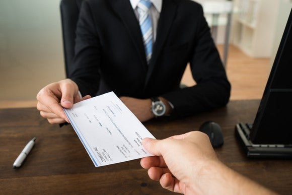 A person in a suit sitting behind a desk handing a paycheck to another person.