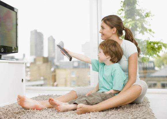A woman and a child sitting on the floor watching television.