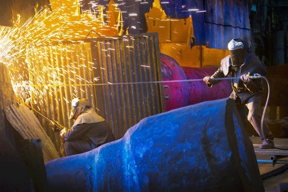 Sparks flying in a steel mill as two workers use equipment.