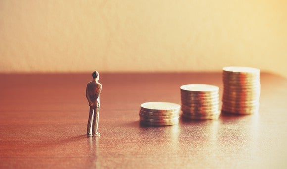 A miniature figurine standing on a table in front of three stacks of coins.
