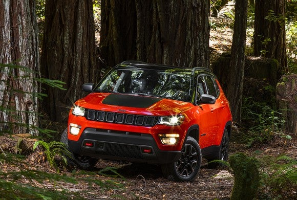 A red 2018 Jeep Compass Trailhawk, a small SUV, shown in the woods.