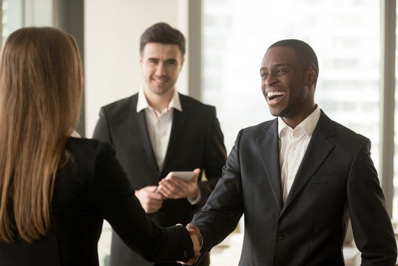 Professional man shaking hands with professional woman as another professional man looks on