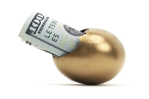 A golden egg with a hundred dollar bill sticking out of a crack in it.