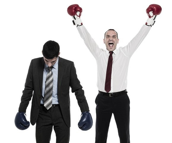 Two men in business suits and boxing gloves.