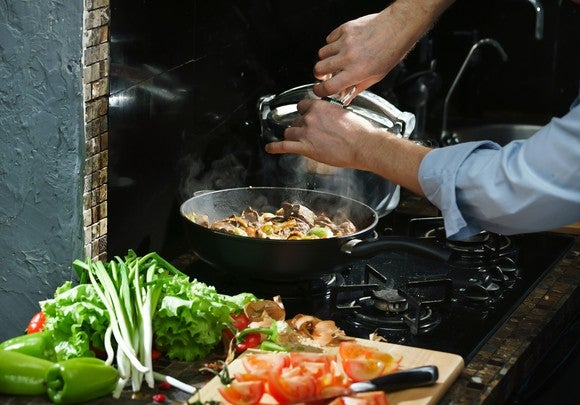 A man adds spice to a pan while cooking.