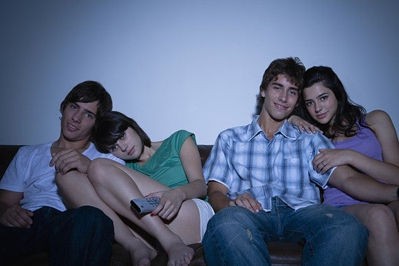 Two couples cuddling on the couch watching TV in a darkened room.