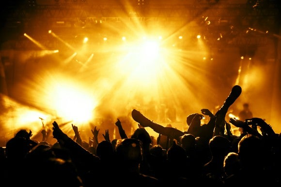 A raucous crowd at a late-night concert event, bathed in yellow spotlights.