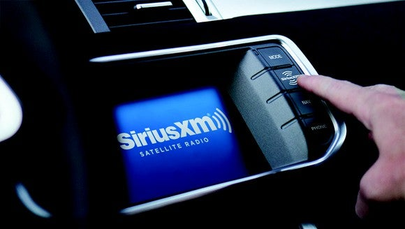 A Sirius XM in-dash radio display inside an automobile.