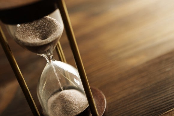 An hourglass on a desk, with half of the sand having moved from the top to the bottom portion.