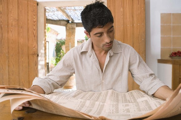 A man closely reading a financial newspaper.