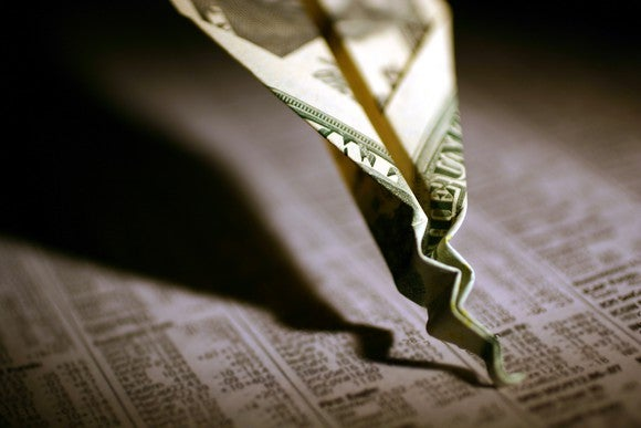 A dollar folded into the shape of a paper airplane that's crashed into the financial section of a newspaper.