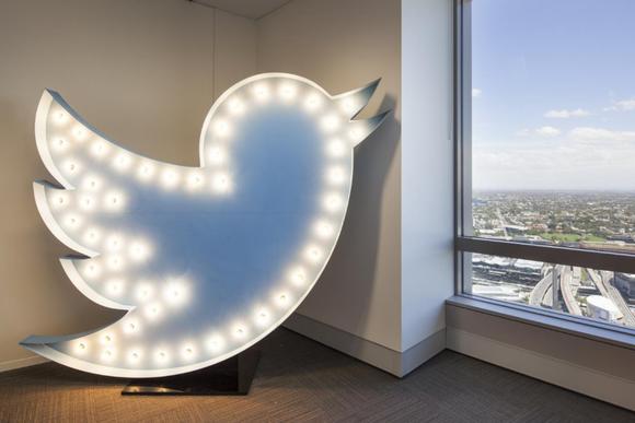 A Twitter logo outlined in lightbulbs by an open window.