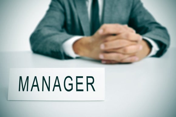 Man in suit with manager sign in front of him