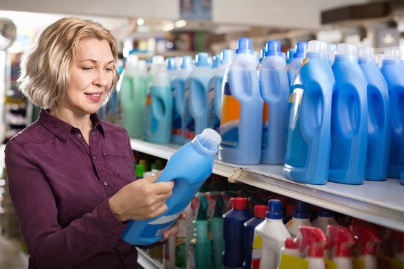 A woman holds a bottle of laundry detergent in front of shelves with cleaning products.