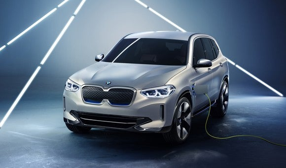 A prototype BMW iX3, a silver compact SUV, is shown plugged into a charger.
