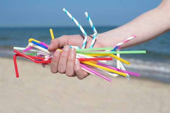 Hand with plastic straws on the beach