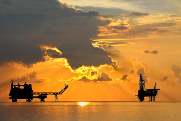 An oil rig and platform at sunset.