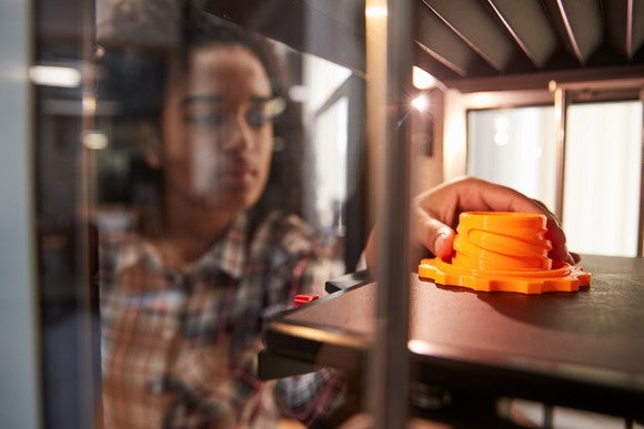 A person 3D printing an orange part.
