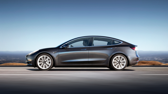 A gray Model 3 on a road next to a body of water