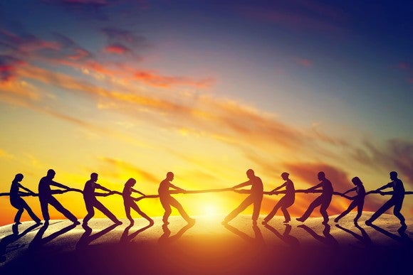 Two groups of people pulling a rope, playing tug of war, with the sunset as a backdrop