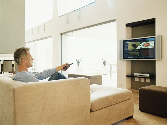 A man sitting on a couch, pointing a television remote at a television.
