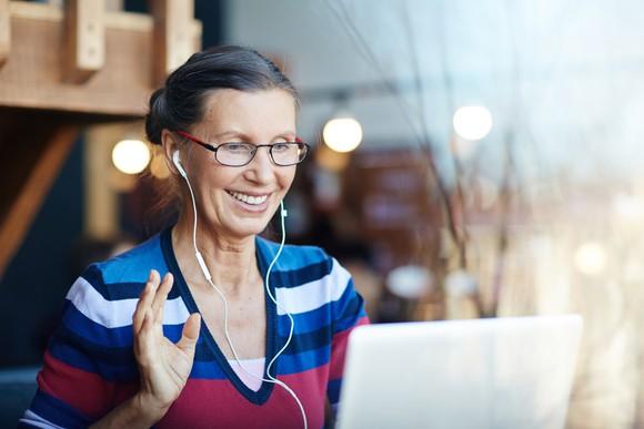 An older woman waving at a laptop screen