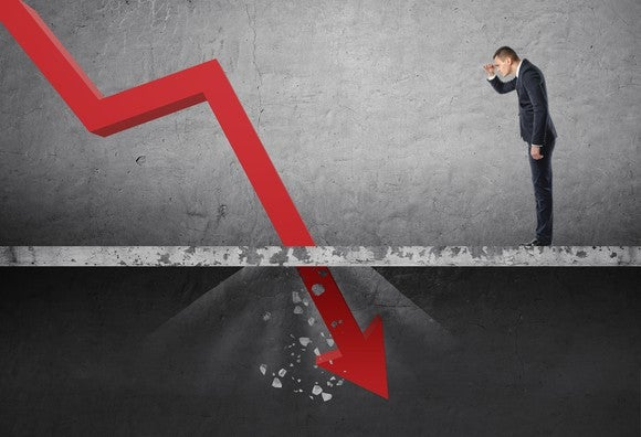 Businessman looking at red line chart plunging through floor