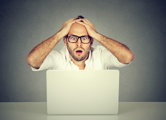 A bespectacled man appearing to be in panic and holding his hands to his head while staring at his laptop.