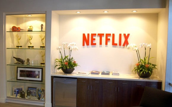 A few shelves displaying a handful of Emmy statuettes and other awards next to a large red Netflix logo.