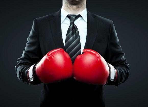 A man in a suit and tie wearing boxing gloves.