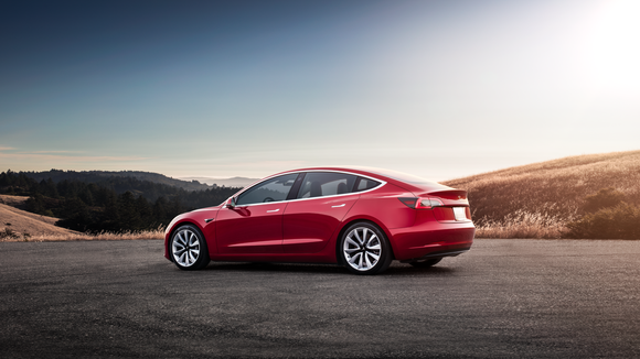 A red Model 3 at sunset