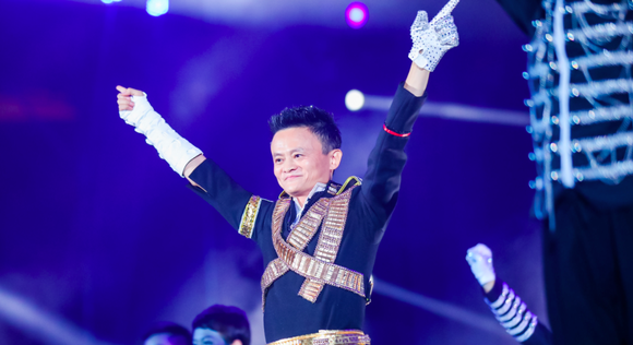 Alibaba founder Jack Ma holds his hands up in victory on stage at an event.