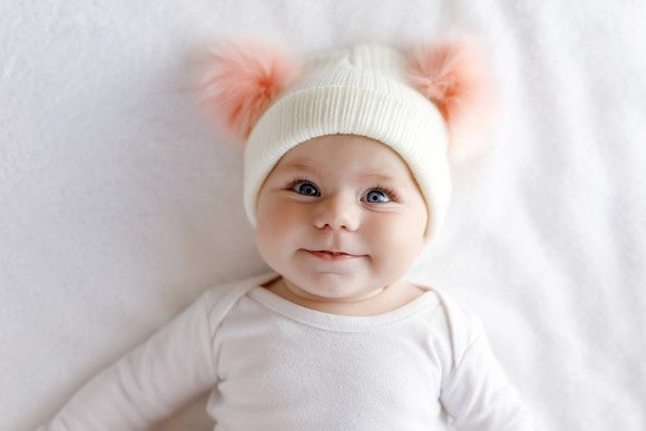 A baby wearing a white knit hat and white shirt while lying on a white sheet.