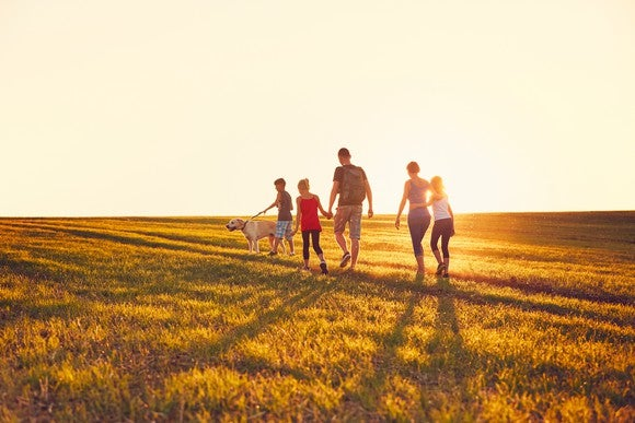 A family and their dog walking in an open field during sunset.